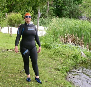 woman in wetsuit, standing on grassy shore