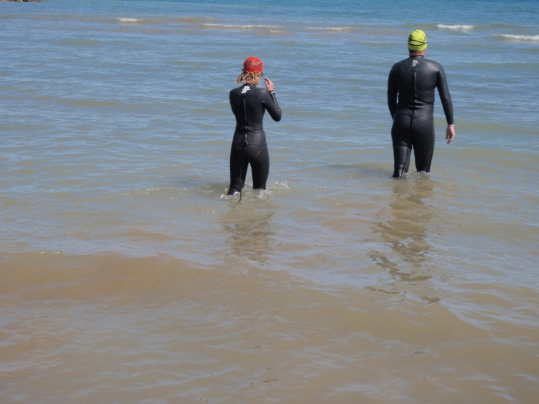 A man and a girl, in wetsuits, wade away from the shore