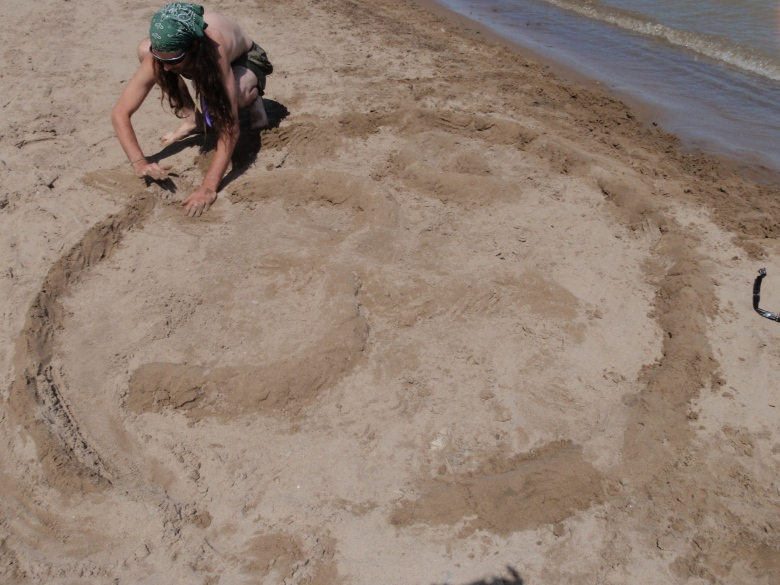 a young man sculpts a Hindu symbol in sand on the beach