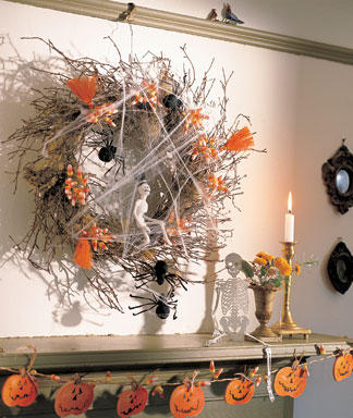 wreath of twigs hanging on a wall, decorated with halloween items
