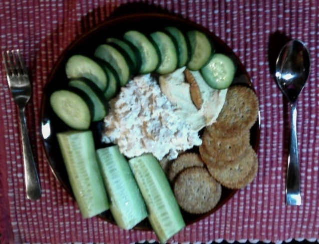 plate of food, crackers, fish, hummus, sliced cucumber