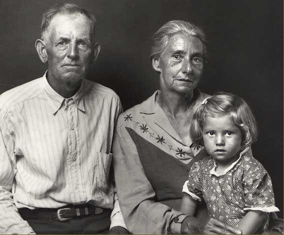 elderly, careworn man and woman with solemn young girl, possibly their granddaugher. All are clean and well dressed