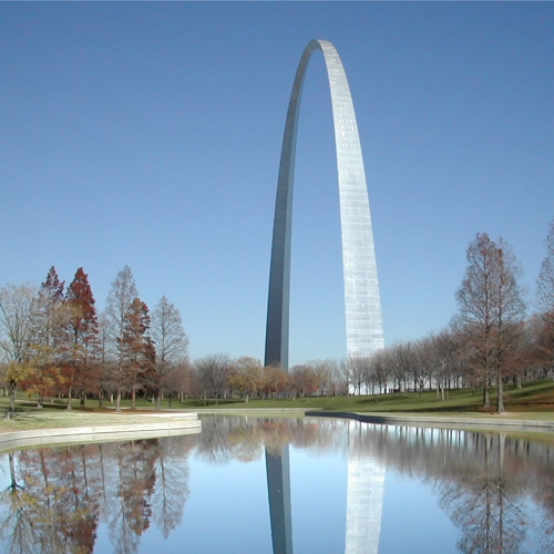 the St. Louis hyperbolic arch against a blue sky and reflected in a pool