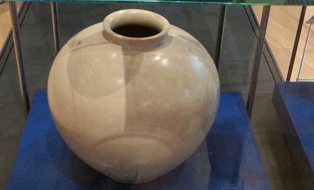 a large, smooth, round vase of beige pottery