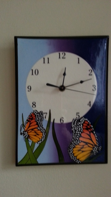 A clock with butterfly decoration