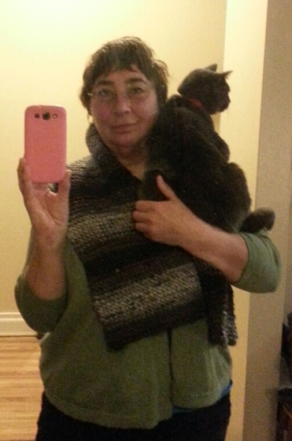 A woman holding a cat and wearing a broad striped scarf smiles as she take a selfie picture