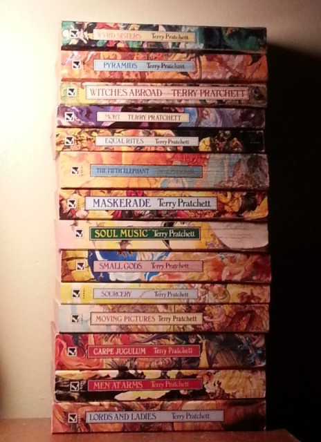 a stack of colourful paperback books by Terry Pratchett