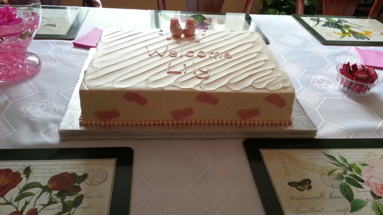 "A flat, rectangular cake, iced and with the inscription, ""Welcome Lily"""