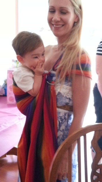 A young woman wears a striped baby sling with a young toddler sitting in it