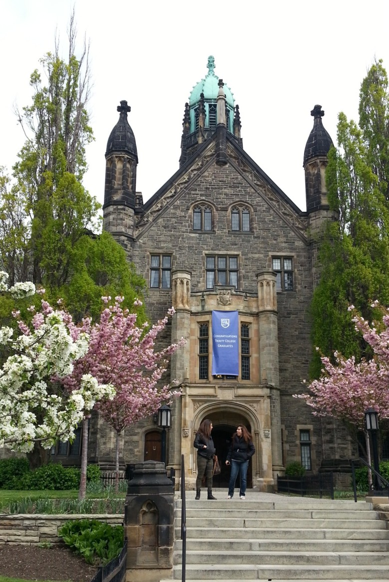 An old stone building flanked by blooming trees