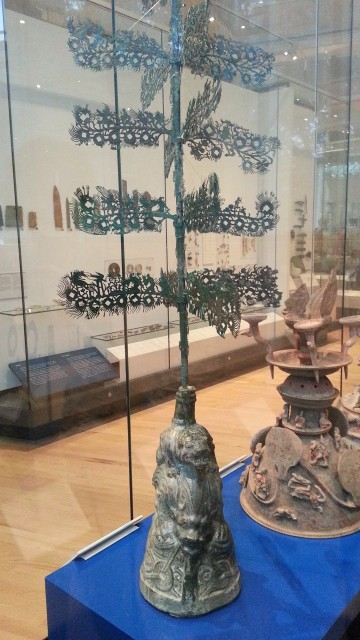 A greenish metal tree in a museum