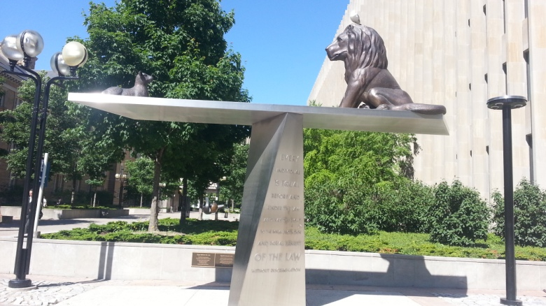 A sculpture like a balance beam has a lion on one side and a lamb on the other, equal before the law
