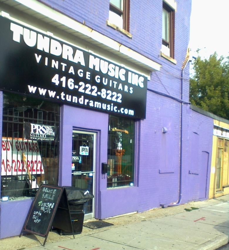 A purple storefront with the sign Tundra Music Inc: Vintage Guitars
