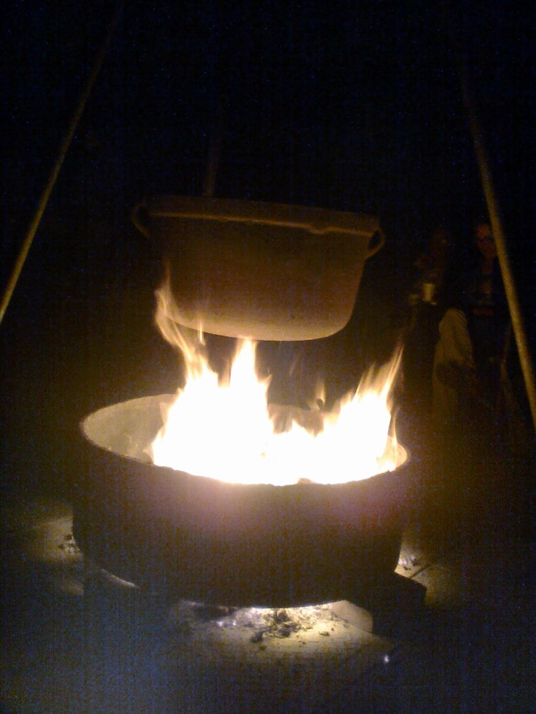 A basin of fire illuminates a pot hanging from a tripod