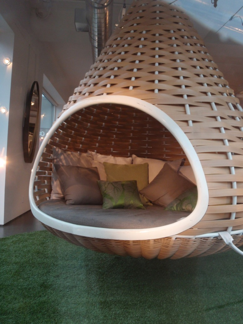 A large wicker cone hangs from the ceiling; it's lined with a mattress and cushions