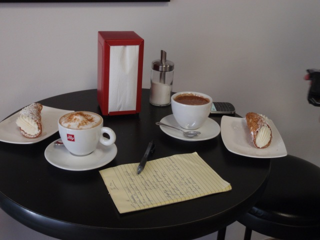 A small table in a restaurant holds two cups of coffee and two cannoli (desserts)