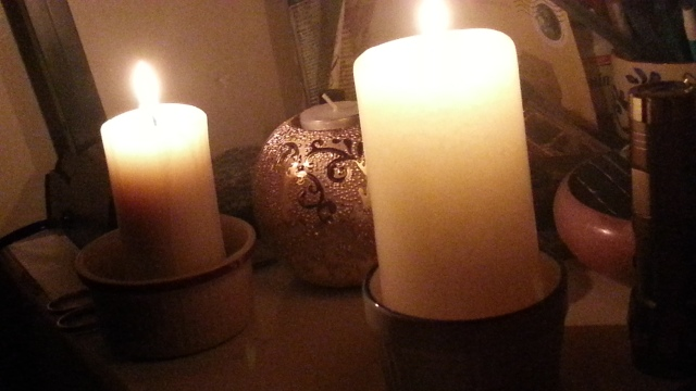 two fat white candles glow on a nightstand