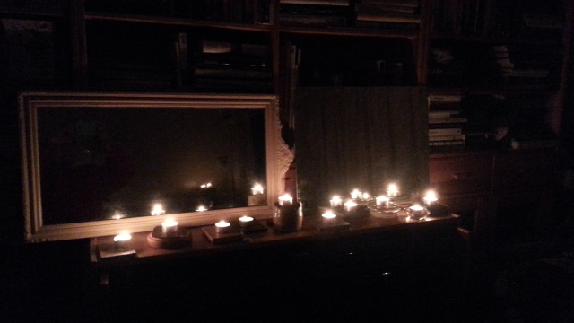 A row of candles on top of a cupboard shine in the darkness