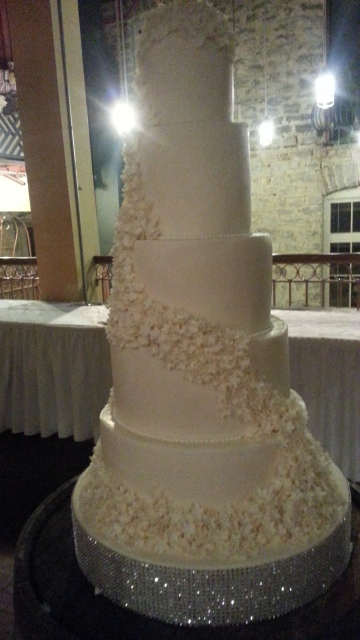 A tall, white wedding cake with several tiers