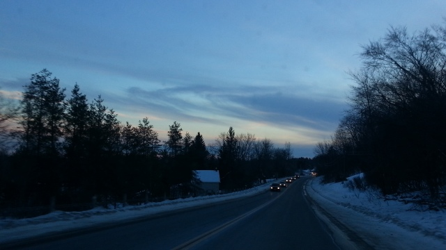 A road stretches away, lined by conifer. It's dusk and a few windblown clouds are in the sky