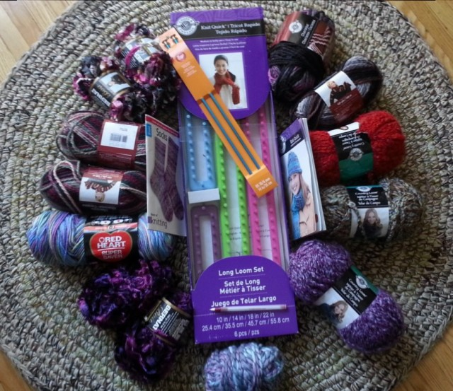 About twelve rolls of yarn in a circle on a circular rug, with a knitting loom and knitting needles in the center
