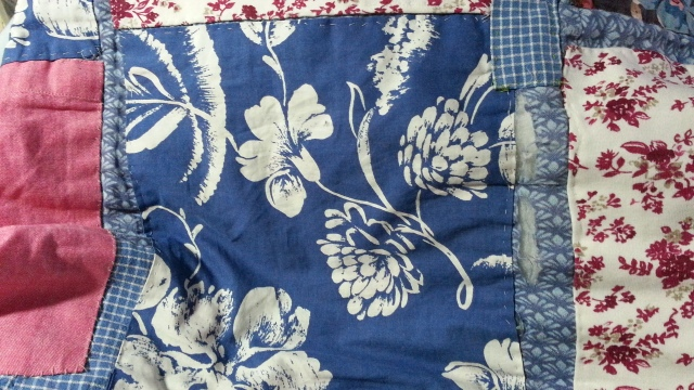 A blue-and-white square n a quilt has some torn cloth beside it, showing the batting