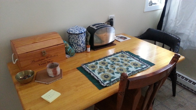 A kitchen table with a few things on it, long side against the wall.