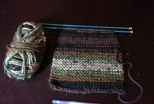 A ball of yarn and a partially knitted scarf in green, grey, and brown