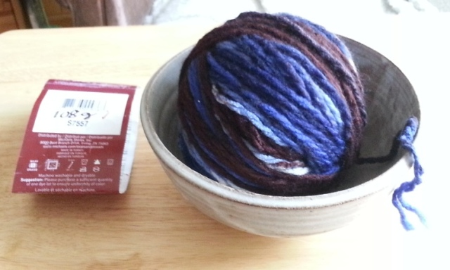 a large ball of blue and brown yarn in a pottery bowl