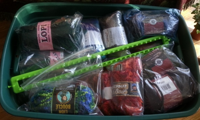 Various colours of yarn in a box, with a knitting loom on top