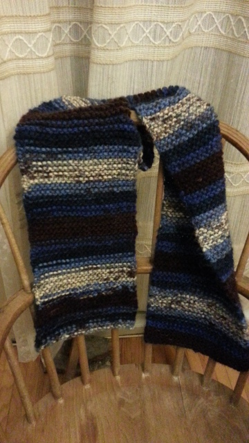 striped blue and brown scarf draped on the back of a wooden chair