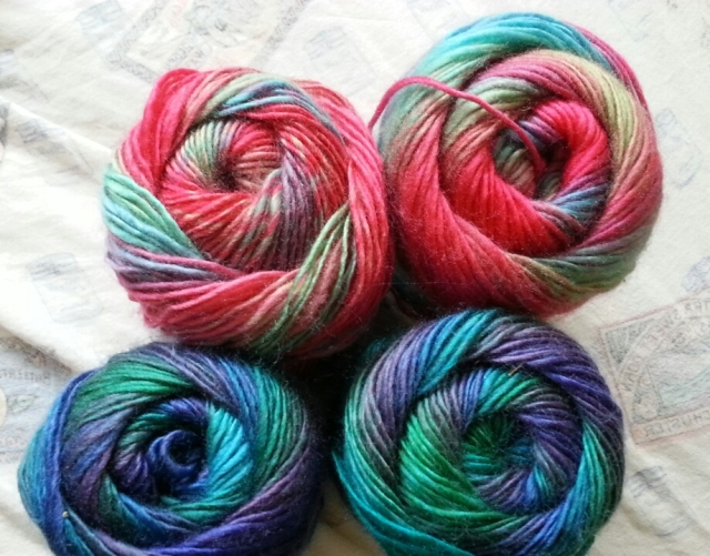 Four skeins of yarn are seen end-on. Two have coral, green and blue swirls; the others have blue, green, and purple.
