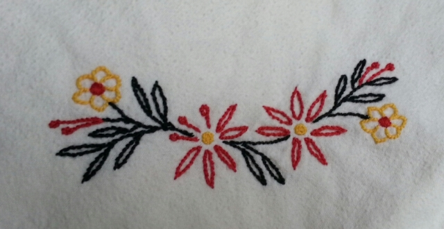 Embroidered flowers in red and gold, with black leaves