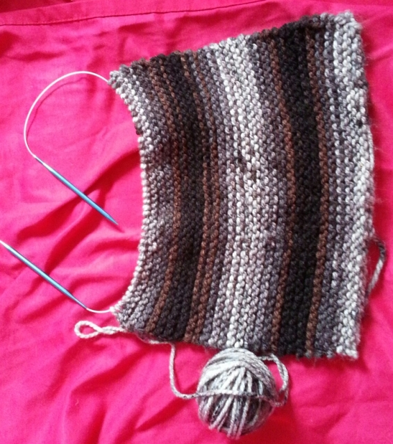a large knitted rectangle in brown, black, and grey