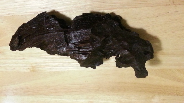 A very dark piece of irregular driftwood