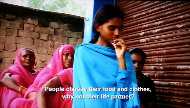A South Asian woman in India asks, People choose their food and their clothes. Why not their life partner? Behind her are several members of the Pink Gang, women who wear pink and fight tradition
