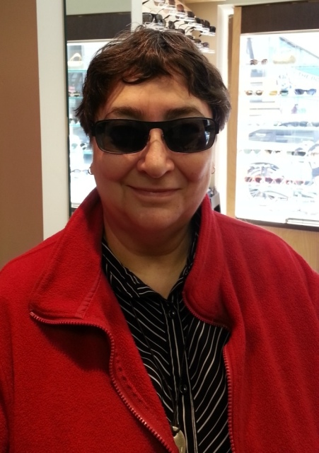 A woman in a red jacket and sunglasses smiles at the camera