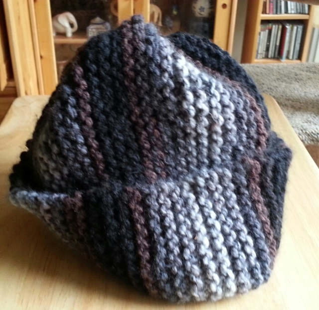 A knitted hat, pyramidal, with a deep brim.