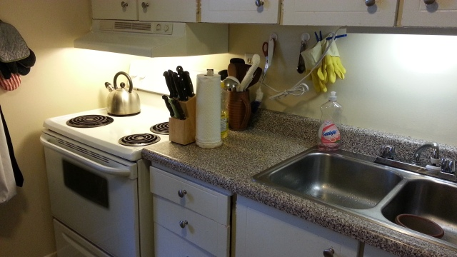 A clean sink, kitchen counter, and stove