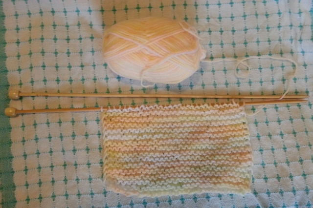 A piece of knitting, rectangular, of white, yellow, and peach yarn