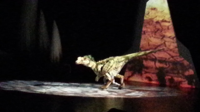 A man in an elaborate dinosaur costume steps into a spotlight
