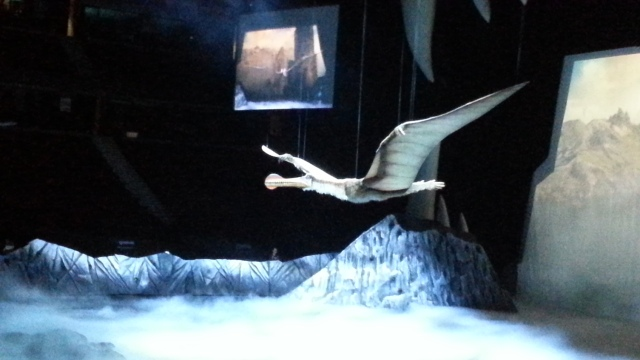 A pterosaur flies over the arena under bluish light
