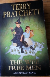 a book, The Wee Free Men. On the cover stands a young girl holding a big book and a frying pan. Beside her is a witch dressed in black holding a contraption of string, twigs, and stones. On the brim of her pointy hat sits a yellow toad. At their feet are several tiny blue men armed with swords. All except the witch are in an attitude of alarm and defence. The witch is watchful.