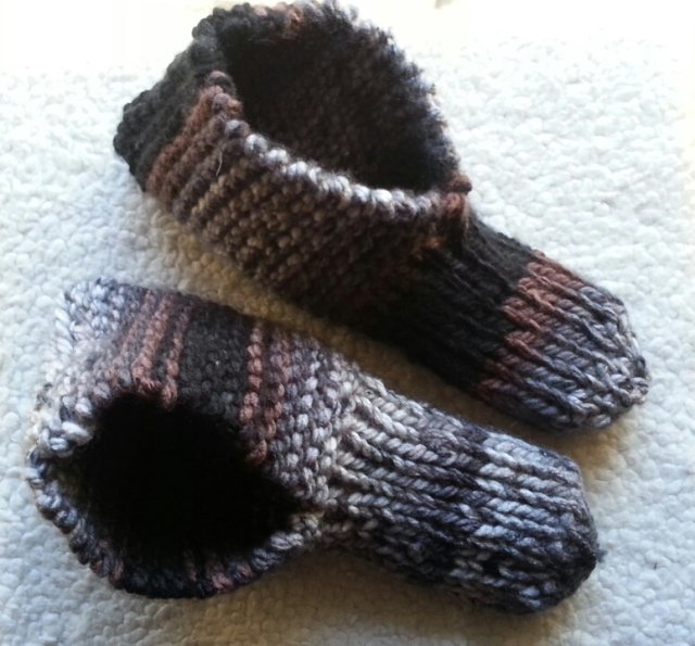 A pair of knitted slippers in brown, grey, and black