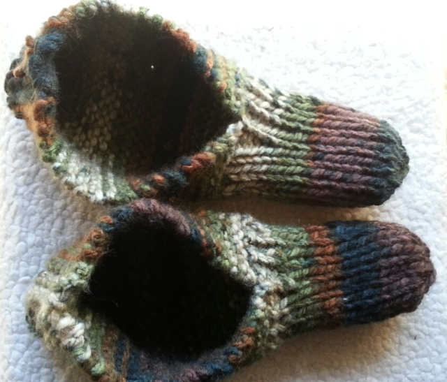 A pair of knitted slippers in green, brown, and black