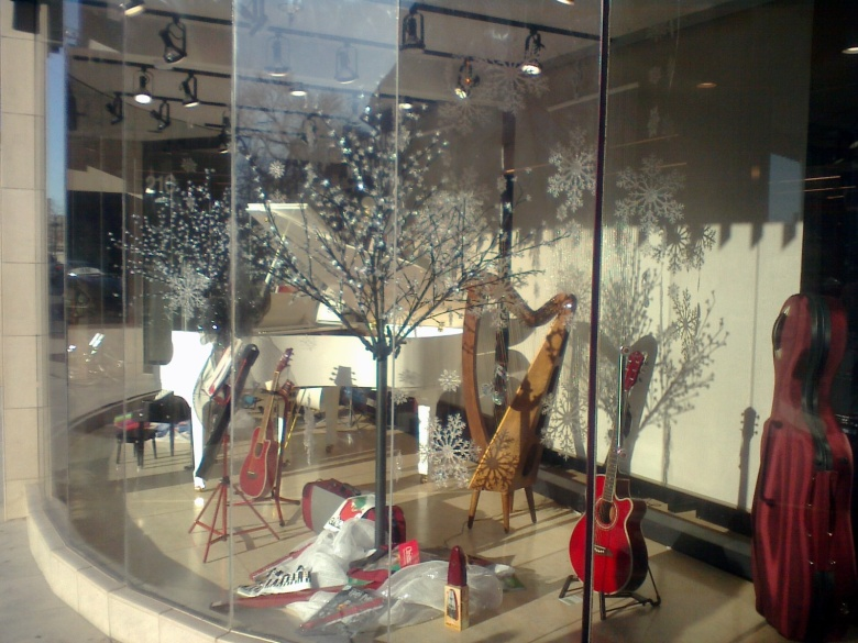 A stre window shows a harp, a celo, guitars, a piano, and trees decorated with crystal flowers