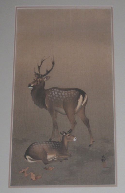 A stag stands by while a doe rets on the ground. Both are dappled with white