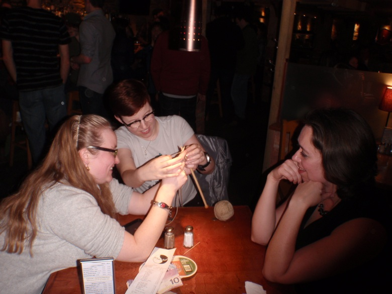 three women sit around a table. Two are trying to knit while one watches