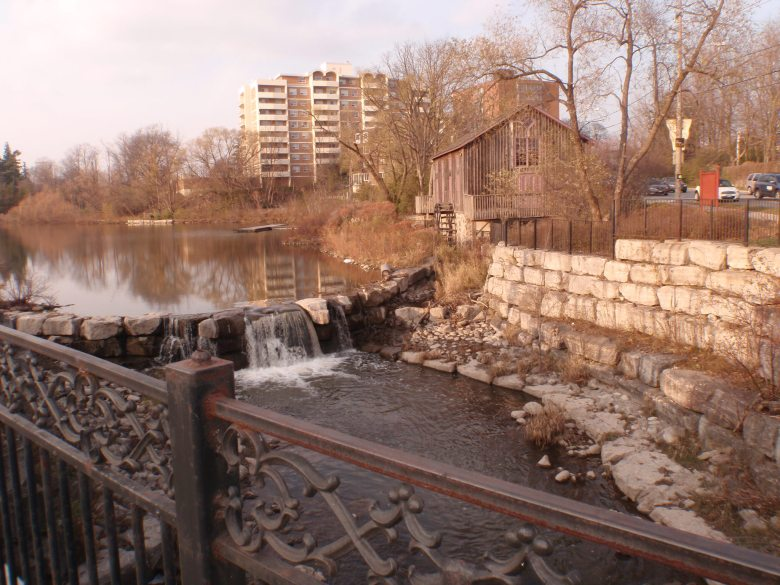 A calm pond beside an old watermill with apartment buildings in the background