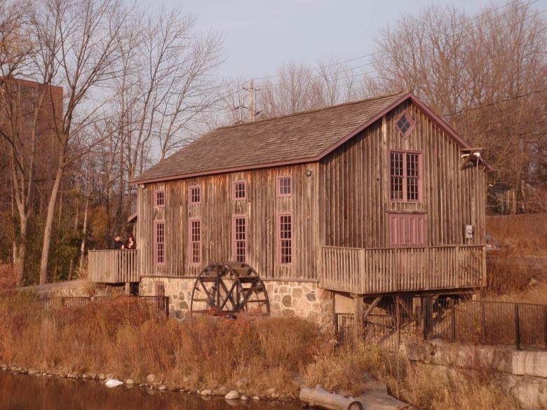 An old wooden building with a stream and a waterwheel beside it.